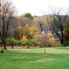 A fall view of green with narrow path in background at Highland Hills Golf Club