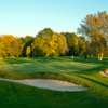 A sunny view of green guarded by bunkers at Winged Pheasant Golf Links