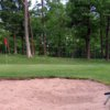 A view of a hole protected by a large sand trap at Luck Golf Course