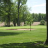 A sunny day view of a green protected by bunkers at Hickory Hills Golf Club