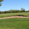 A view of a hole guarded by a bunker at Bow Island Golf Course