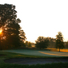 A sunset view of a green protected by bunkers at Brookshire Inn & Golf Club
