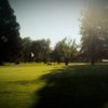 A sunny view of a green at Meadowlawn Golf Club