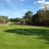 A sunny day view of a green at Pine Ridge Country Club